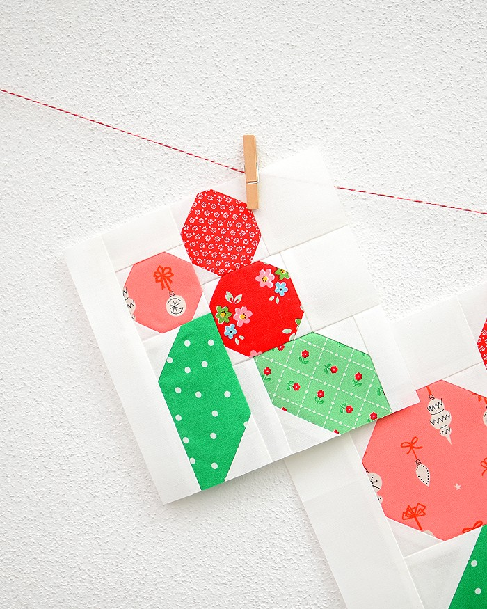 6 Inch Holly Berry quilt block hanging on a wall
