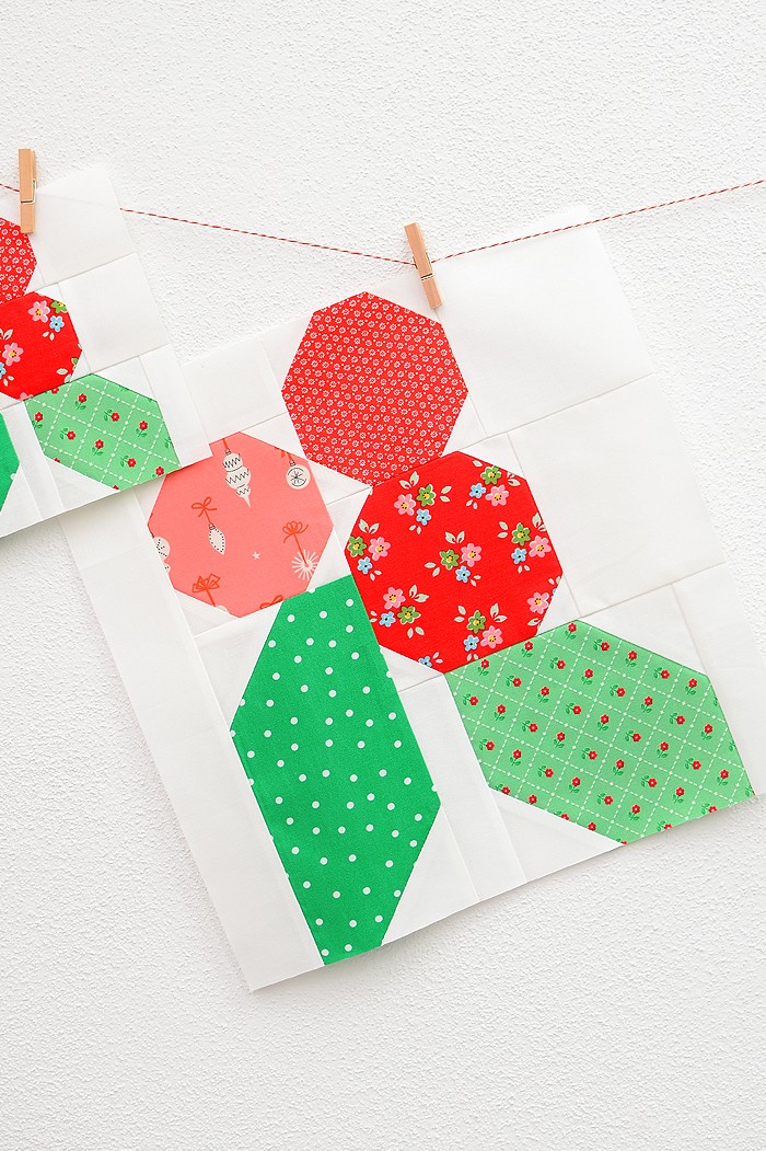 12 Inch Holly Berry quilt block hanging on a wall