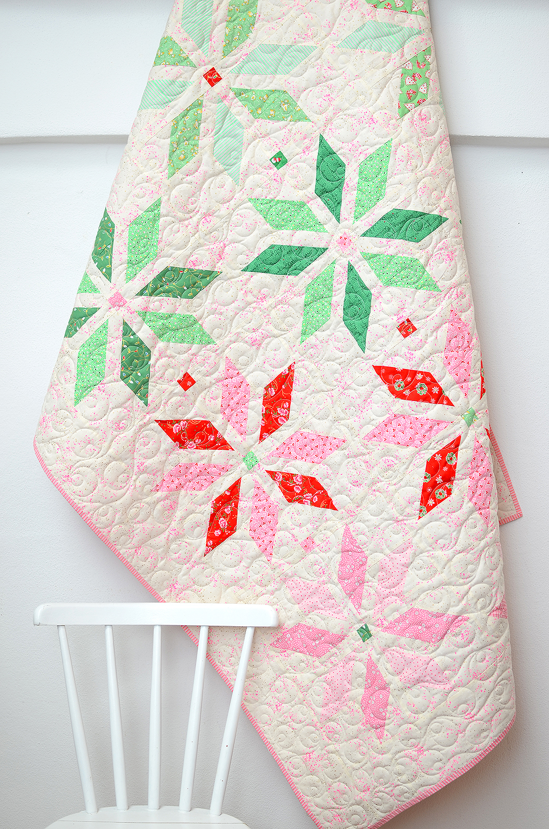 Christmas quilt hanging from a wall, a chair in the front